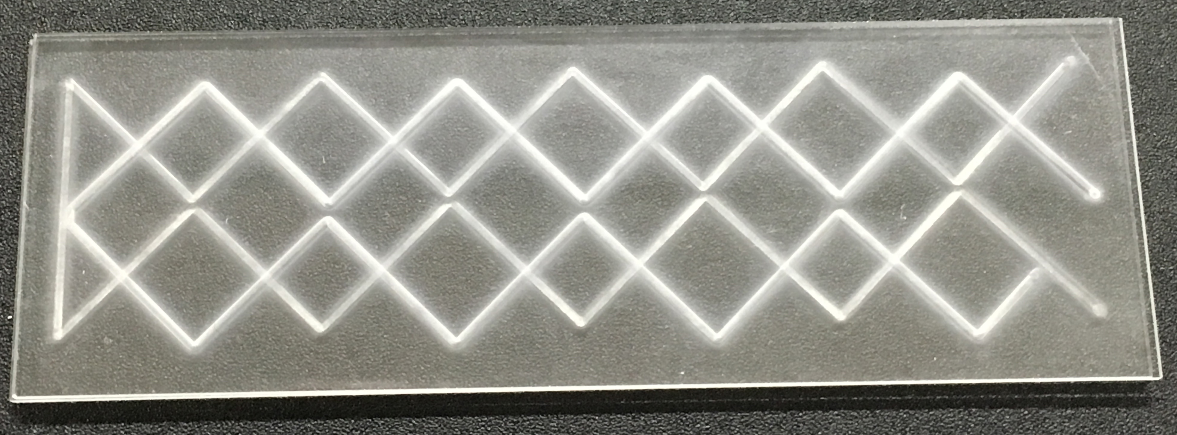 Etch channels of precise depth into glass slides for microfluidics using micro-precision sandblasting.